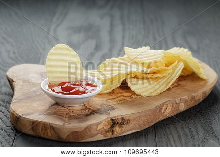 salted potato ships with sauce on old wooden table