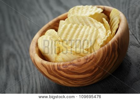 bowl full of salted potato ships on old wooden table