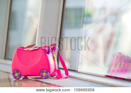 Closeup pink small suitcase with passport and boarding pass in airport near window