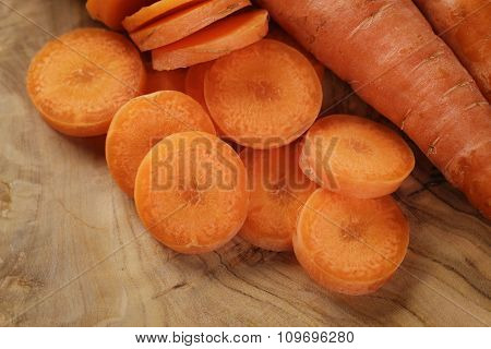 sliced organic carrot on olive wood cutting board