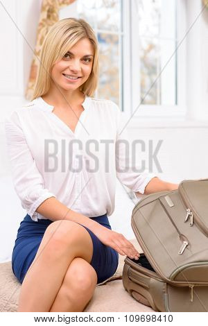 Young lady unpacking her baggage.