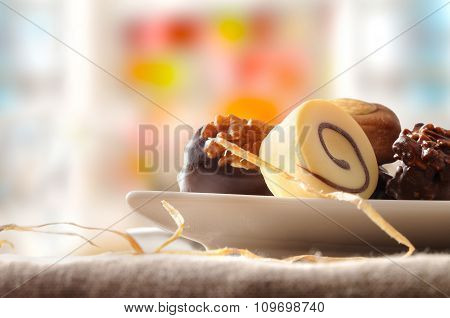 Assorted Bonbons In White Dish And Colorfull Background Front View