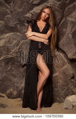 Beautiful and sexy woman in black peignoir with long hair on the beach with rocks
