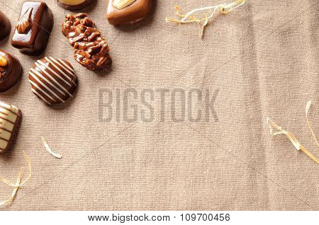 Assorted Bonbons On Tablecloth Fabric With Straw Decoration Top
