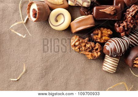 Group Of Bonbons Stacked On Tablecloth Fabric With Straw Decoration Top