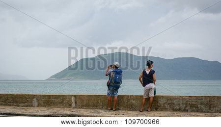 Young Men Standing And Seeing The Sea