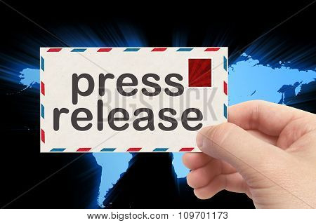 Hand Holding Envelope With Press Release Word And World Background