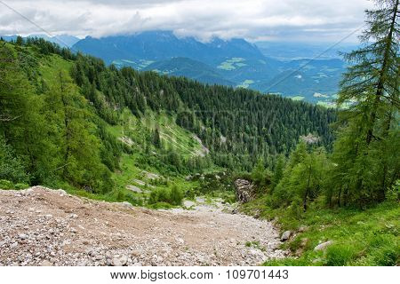 Scenic View of Steep Dirt Mountain Path Leading Down Mountain Side Through Lush Green Forest, Berchtesgade, Bavarian Alps, Germany
