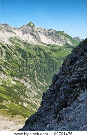 Mountainous scenery with two steep slopes, one dark and one sunny, at high altitude, Hochvogel mountain, Alps