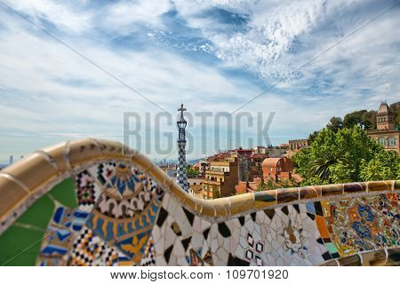 Detail of a mosaic wall with colorful inlaid ceramic tiles on the main terrace, Parc Guell, Barcelona, Spain