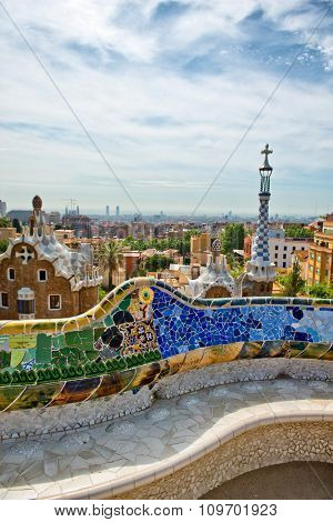 Detail of the colorful ceramic mosaics on the undulating wall above the public benches at Parc Guell, Barcelona, Spain with a view of the architecture of the park behind