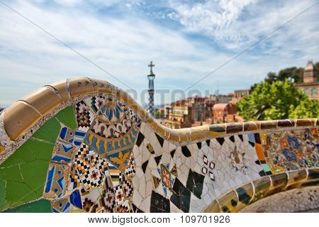 Detail of a mosaic wall with colorful inlaid ceramic tiles on the main terrace, Parc Guell, Barcelona, Spain, designed by Antoni Gaudi