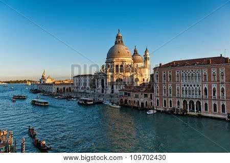 Basilica Santa Maria della Salute, Venice, Italy at sunset with boat traffic, including a vaporetto or water bus, in the Grand Canal