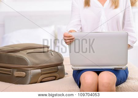 Hotel resident sitting on bed and using laptop.