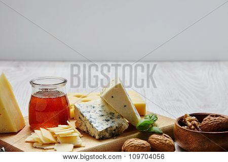 Cheese Board With Nuts Basil And Honey In Front Od Display Board
