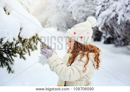 Little Girl Decorates The Christmas Tree.