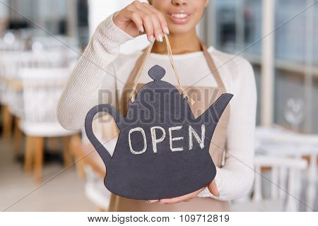 Waitress holding an opening sign.