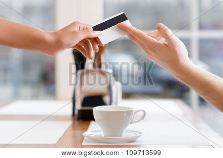 Waitress is taking credit card from a client.