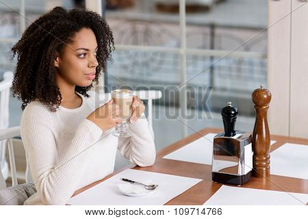 Young lady is drinking coffee.