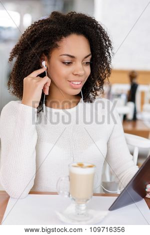 Young woman using tablet and headphones.