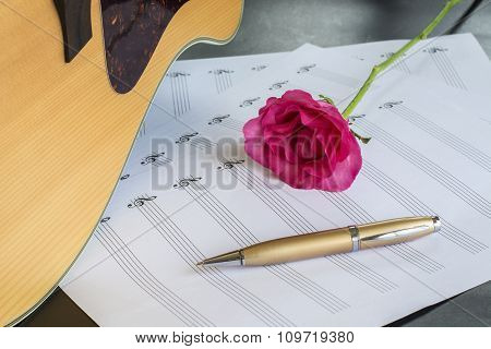 Guitar with pen and rose on the note bookvintage filter