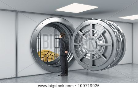 Young Man Standing In Front Of A Big Unlocked Round Metal Safe In A Bank With A Pyramid Of Gold Bars