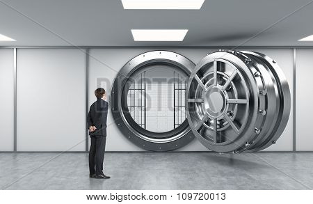 Young Man Standing In Front Of A Big Unlocked Round Metal Safe In A Bank With Lock-boxes Inside In A