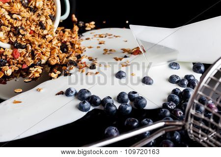 Yogurt blueberries granola mixed on black from side