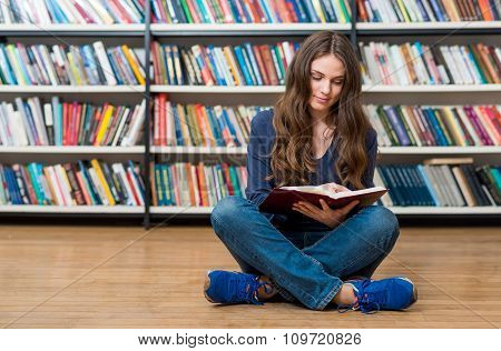Smiling Young Girl Sitting On The Floor In The Library With Crossed Legs, With An Open Book On Her K