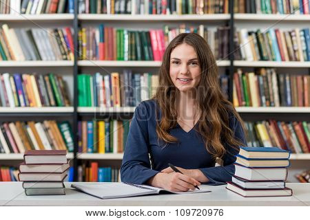 Smiling Young Girl Sitting At A Desk In The Library With An Open Note Book Making Notes, Piles Of Bo