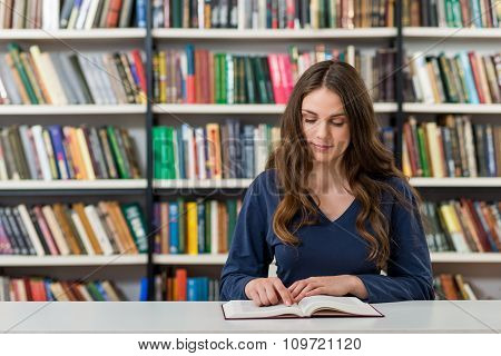 Smiling Young Girl With Loose Long Dark Hair  Sitting At A Desk In The Library With An Open Book Rea