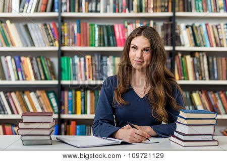 Smiling Young Girl With Loose Long Dark Hair Sitting At A Desk In The Library With An Open Note Book