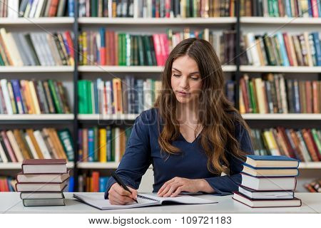 Serious Young Girl With Loose Long Dark Hair Sitting At A Desk In The Library With An Open Note Book