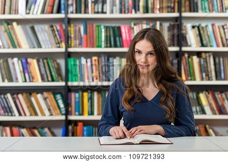 Smiling Young Girl With Loose Long Dark Hair  Sitting At A Desk In The Library With An Open Note Rea