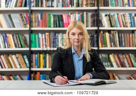 Young Girl With Loose Blonde Hair  Sitting At A Desk In The Library With An Open Note Book Writing,