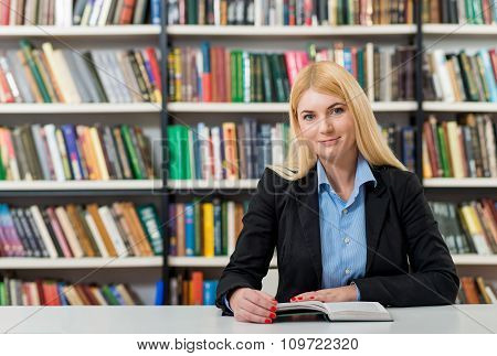 Smiling Young Girl With Blonde Hair  Sitting At A Desk In The Library With An Open Book Reading, Loo