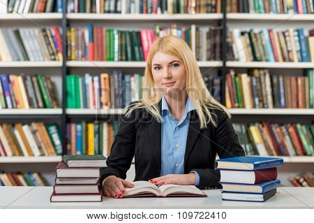 Blonde Young Girl Sitting At A Desk In The Library With Piles Of Books On Both Sides Of The Desk Rea
