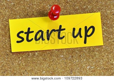 Start Up  Word On Yellow Notepaper With Cork Background