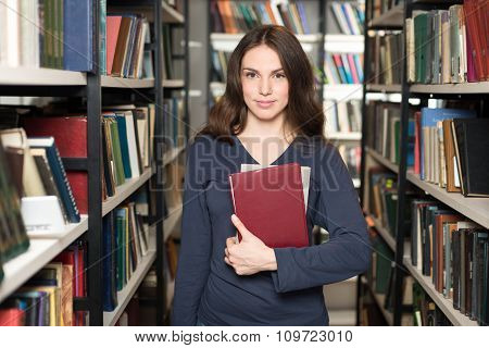 Smiling Young Lady With Loose Long Dark Hair Standing And Holding Two Books Between Book Shelves In