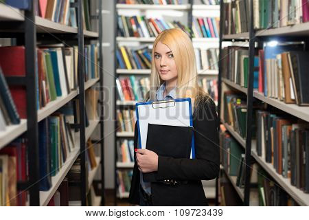 Young Lady With Blond Hair Standing And Holding A Black Copy Book And A Note Pad Between Book Shelve