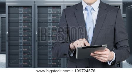 Young Man With A Tablet In Front Of Server For Data Storage, Processing And Analysis, Rows Of Machin