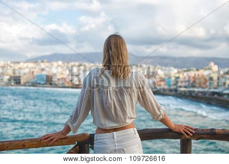 Woman looking at cityscape with bay. From the back. Place for your text.