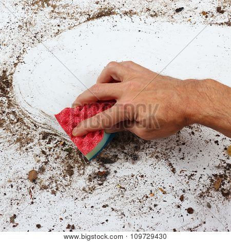 Hand with sponge cleans very dirty surface