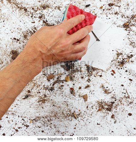 Hand with red sponge cleans dirty surface
