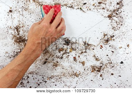 Hand with red sponge cleans very dirty surface