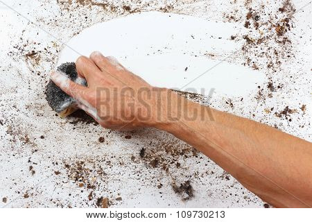 Hand with wet sponge wiping dirty surface