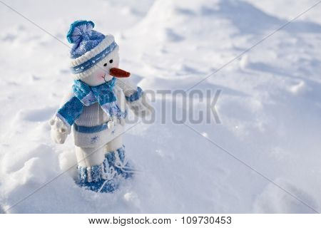 Little snowman with carrot nose in the snow.