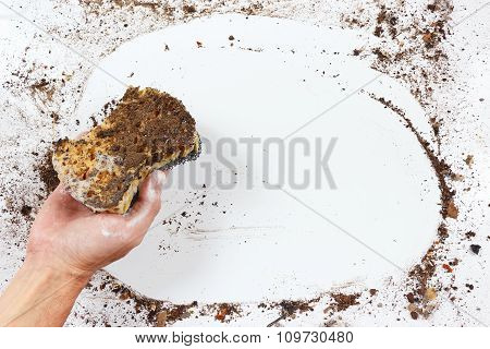 Hand with wet black sponge cleans heavily dirty surface