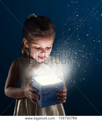 Little girl opens a gift. It is lit from within. Dark - blue background.