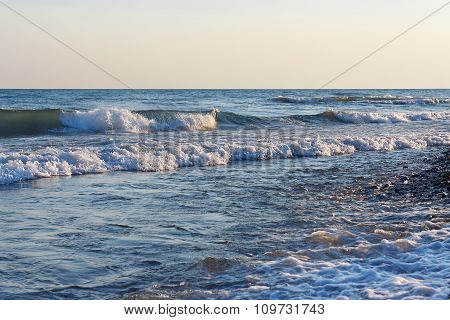 Tranquil surf waves on the beach against clear sky